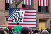 """Brooklyn, NY - 2 March 2019. A sign reading """"Still Here"""" is raised in front of the American flag at Bernie Sanders' first rally for the 2020 presidential primary at Brooklyn College."""