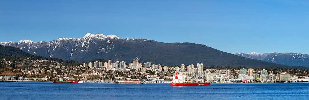 View of North Vancouver and Mount Seymour from downtown Vancouver.  The ship in Burrard Inlet is the American Bulker (Panama) likely carrying Canadian grains from North Vancouver.  Photographed from the Vancouver Trade and Convention Center in Vancouver, British Columbia, Canada