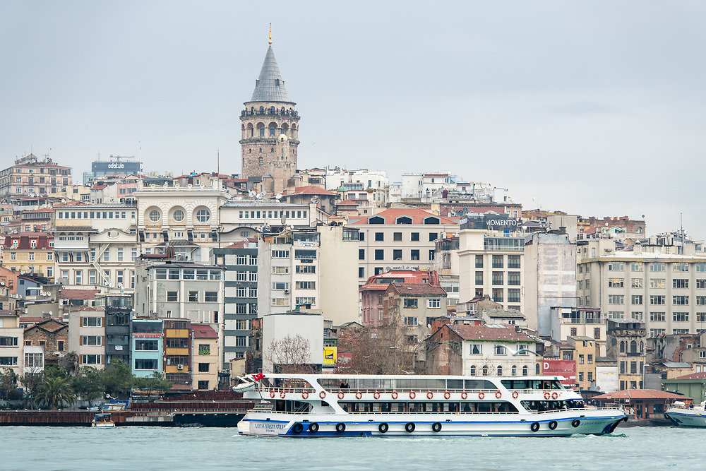 The Galata Kulesi, a medieval tower built by the Byzantines, rises above the city skyline, as a ferry boat floats across the Golden Horn in Istanbul, Turkey