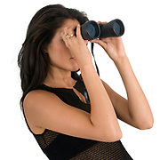 Woman looks through a binoculars trying to foresee the future