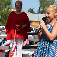 "Piper Schoolar sings ""God Bless the U.S.A."" to open the ceremonies of an open house for Aberdeen Main Street's depot, located alongside Chestnut Street."