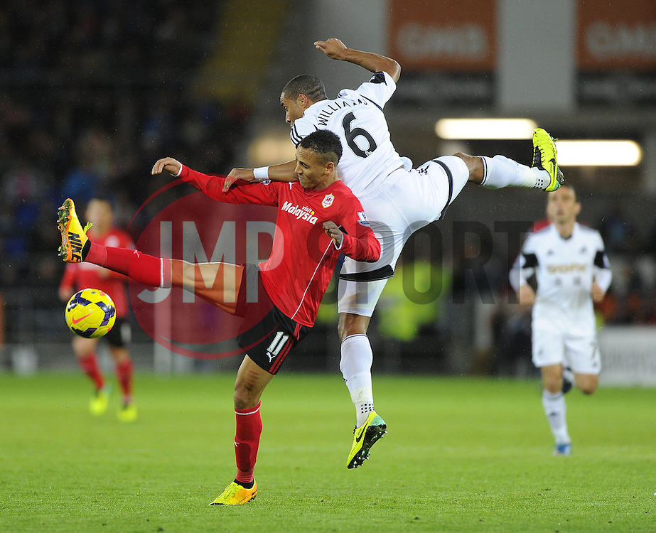 Cardiff City's Peter Odemwingie battles for the high ball with Swansea City's Ashley Williams - Photo mandatory by-line: Joe Meredith/JMP - Tel: Mobile: 07966 386802 03/11/2013 - SPORT - FOOTBALL - The Cardiff City Stadium - Cardiff - Cardiff City v Swansea City - Barclays Premier League