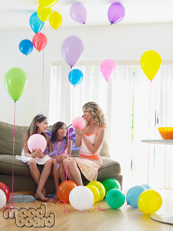 Two girls (7-9 10-12) with mother sitting on sofa in room full of balloons