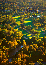 Stock photo of an aerial view of the Houston, Texas River Oaks Country Club golf course and Buffalo Bayou as it flows by Memorial Park at sun set.