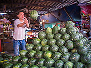 "03 APRIL 2014 - BANGKOK, THAILAND:    A vendor stacks watermelons in a stand in Khlong Toey Market. Khlong Toey (also called Khlong Toei) Market is one of the largest ""wet markets"" in Thailand. The market is located in the midst of one of Bangkok's largest slum areas and close to the city's original deep water port. Thousands of people live in the neighboring slum area. Thousands more shop in the sprawling market for fresh fruits and vegetables as well meat, fish and poultry.     PHOTO BY JACK KURTZ"
