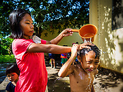20 JANUARY 2018 - CAMALIG, ALBAY, PHILIPPINES: A woman bathes her son at a well in the Barangay Salugan evacuee shelter in a school in Camalig. There are about 870 people living at the shelter. They won't be allowed to move back to their homes until officials determine that Mayon volcano is safe and not likely to erupt. More than 30,000 people have been evacuated from communities on the near the Mayon volcano in Albay province in the Philippines. Most of the evacuees are staying at school in communities outside of the evacuation zone.   PHOTO BY JACK KURTZ
