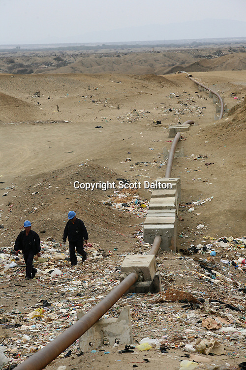 Workers walk by an oil pipeline on the outskirts of Talara, on Peru's northern coast on November 10, 2007. Talara is one of Peru's main oil producing regions and the Chinese company SAPET has an oil field in the region. (Photo/Scott Dalton)