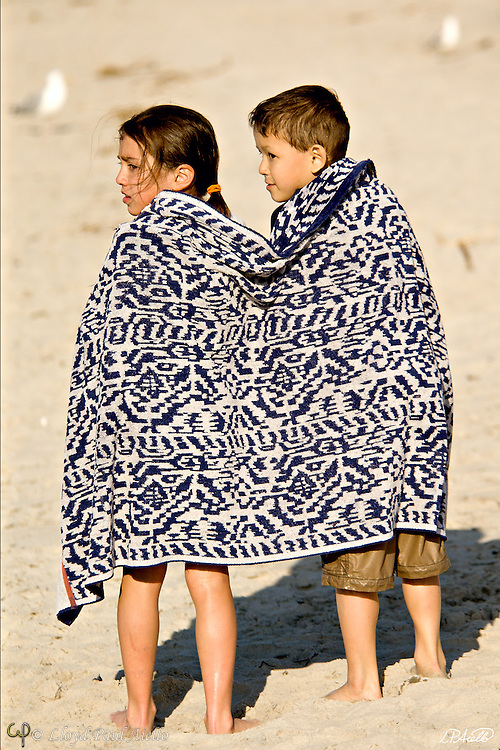 AJ (age 8) and LB (age 6) share a warm towel after a springtime ocean swim at Crane Beach in Ipswich, Massachusetts.