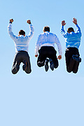 Group of mature businessmen jumping on office rooftop