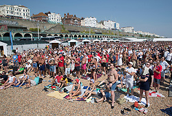 i© Licensed to London News Pictures. 07/07/2018. Brighton, UK. Football fans on the beach in Brighton watch a giant TV screen showing England's 2-0 quarter-final win over Sweden at the Russian World Cup. Photo credit: Peter Macdiarmid/LNP