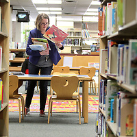 Grace Hall, Lee County Library children's librarian, picks up books to put back on the shelf after children's storytime at the Library. Children's story time is at 10 am every Thursday and open to the public.