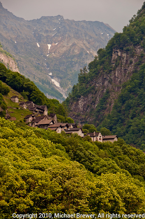 A small mountain village is perched on the slopes of the green, forested  mountainside in Valle Verzasca, Ticino, Switzerland.