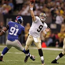 2009 October 18:  New Orleans Saints quarterback Drew Brees (9) throws as New York Giants defensive end Justin Tuck (91) pressures during the first half at the Louisiana Superdome in New Orleans, Louisiana.