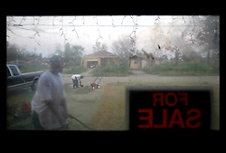 20 August 2006 - New Orleans - Louisiana. Lower 9th ward. Jerome Benjamin (with weed-eater) and Louis Banks (mower) work to reign in the weeds at an abandoned Lower 9th ward property with flood grime thick on the windows, thick on everything that belongs to an elderly lady the men know as 'Grandma.' Everyone knew 'Grandma,' they say. Her real grandson was supposed to come by and get the gutted home ready for sale. He never showed up. The neighbourhood is deserted. It is hard to imagine anyone living here ever again.
