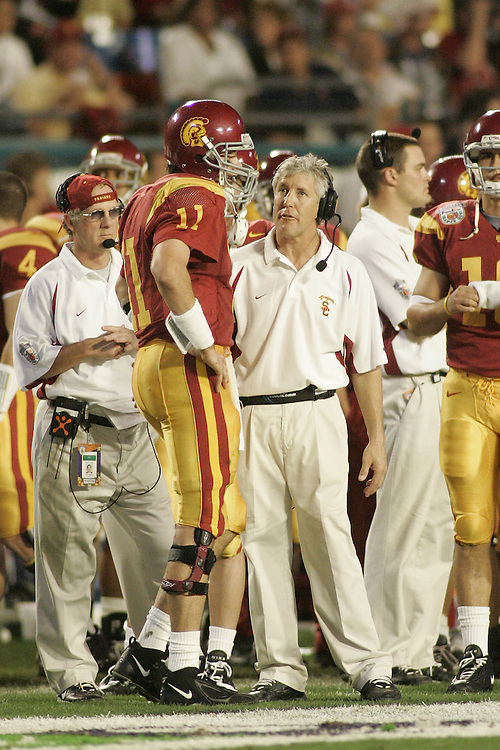 University of Southern California head coach Pete Carroll chats with quarterback Matt Leinart during USC's 55-19 victory over Oklahoma on January 4, 2005 in the FedEx Orange Bowl at Pro Player Stadium in Miami, Florida.