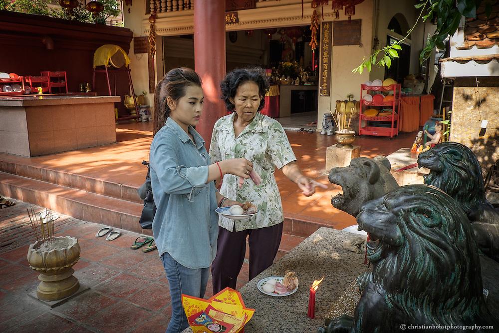 Eine junge Frau bringt in der Tempelanlage im Wat Phnom eine Opfergabe. Die Tempelanlage Wat Phnom ist das spirituelle Zentrum der Stadt Phnom Penh und wird von deren Einwohnern täglich zum Gebet aufgesucht. Die Anlage gilt als eine der Top  Sehenswürdigkeiten der Stadt und wird deshalb auch rege von Touristen besucht.