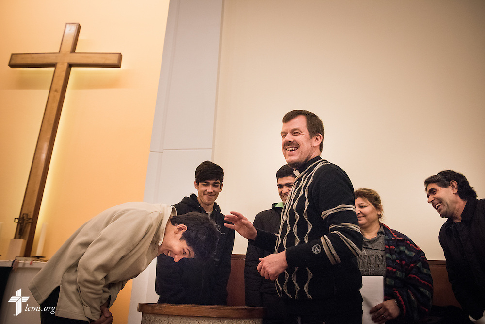 The Rev. Dr. Gottfried Martens shares a laugh with an Afghani family during a baptism rehearsal on Saturday, Nov. 14, 2015, at the Dreieinigkeits-Gemeinde, a SELK Lutheran church in Berlin-Steglitz, Germany.  The refugees completed 3-months of intensive instruction before their baptism. LCMS Communications/Erik M. Lunsford