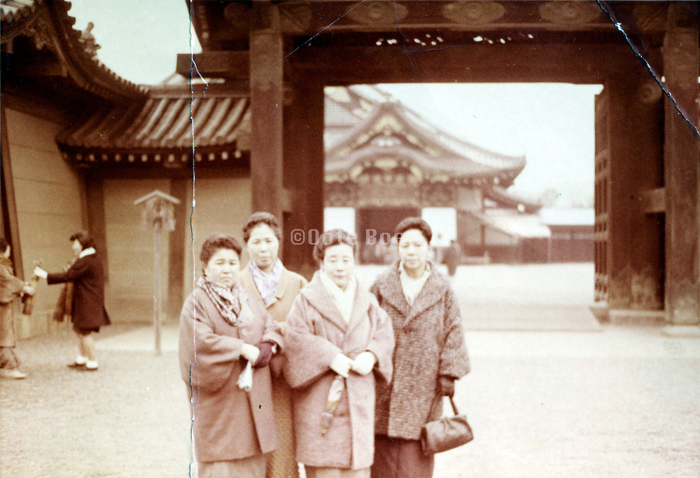 posing by the gates entrance to a temple Japan late 1950s