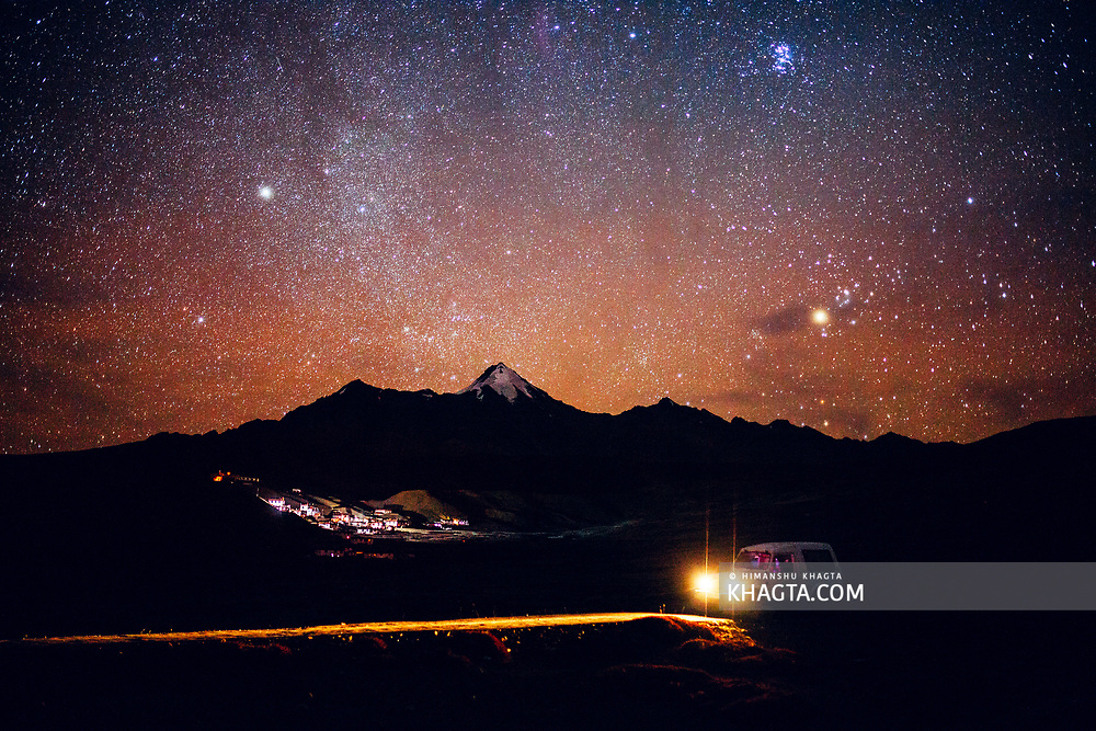 On a dark stary night, a car moves in front of Langza village of Spiti, Himachal Pradesh, India