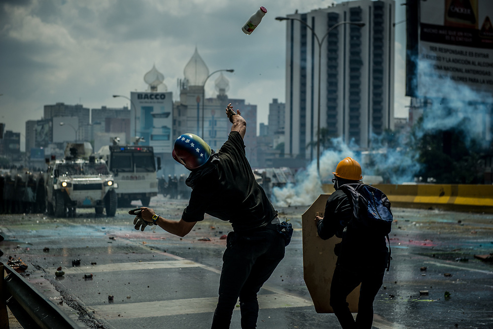 CARACAS, VENEZUELA - MAY 10, 2017:  Anti-government protesters hurl glass jars full of paint during clashes for control of the Francisco Fajardo highway with members of the National Police, who responded with a water cannon, and by heavily tear gassing and firing rubber bullets and buckshot at them.  The streets of Caracas and other cities across Venezuela have been filled with tens of thousands of demonstrators for nearly 100 days of massive protests, held since April 1st. Protesters are enraged at the government for becoming an increasingly repressive, authoritarian regime that has delayed elections, used armed government loyalist to threaten dissidents, called for the Constitution to be re-written to favor them, jailed and tortured protesters and members of the political opposition, and whose corruption and failed economic policy has caused the current economic crisis that has led to widespread food and medicine shortages across the country.  Independent local media report nearly 100 people have been killed during protests and protest-related riots and looting.  The government currently only officially reports 75 deaths.  Over 2,000 people have been injured, and over 3,000 protesters have been detained by authorities.  PHOTO: Meridith Kohut