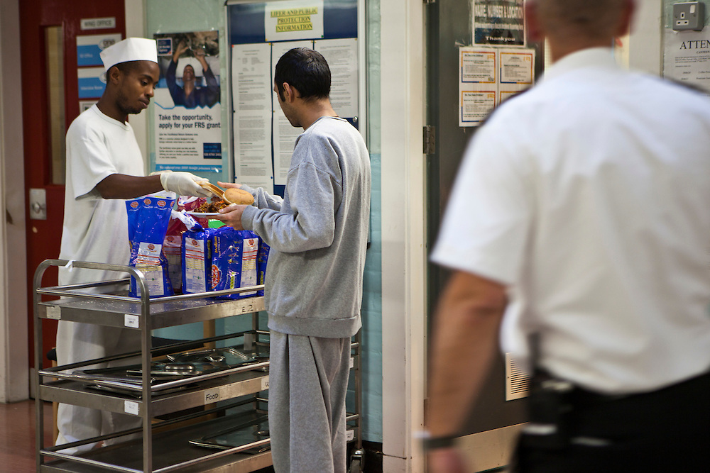 A kitchen orderly serves lunch to another prisoner  on E wing. HMP Wandsworth, London, United Kingdom