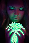 Portrait of a woman holding a glowing green sponge.Black light
