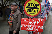 On the day that the EU in Brussels agreed in principle to extend Brexit until 31st January 2020 (aka 'Flextension') and not 31st October 2019, a bystander passes a Remainer's 'Stop Brexit, Revoke Artocle 50' lollipop and a Brexiter's 'I'll Never Vote Conservative Again' placard during a Brexit protest outside parliament, on 28th October 2019, in Westminster, London, England.