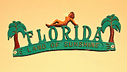 "Palm trees and a nude decorate a vintage (possibly 1940s or '50s), metal,  ""Florida Land of Sunshine"" sign fixed to an outside wall of a small apartment building in Miami Beach's North Beach neighborhood"