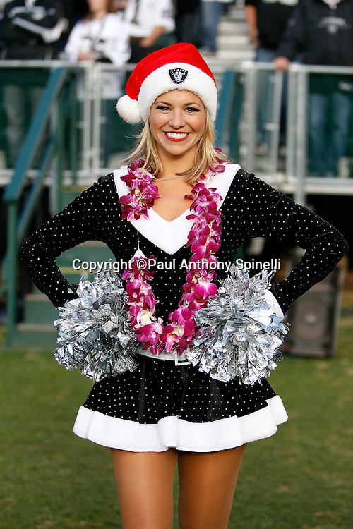 An Oakland Raiders Raiderette cheerleader smiles during the NFL week 15 football game against the Detroit Lions on Sunday, December 18, 2011 in Oakland, California. The Lions won the game 28-27. ©Paul Anthony Spinelli