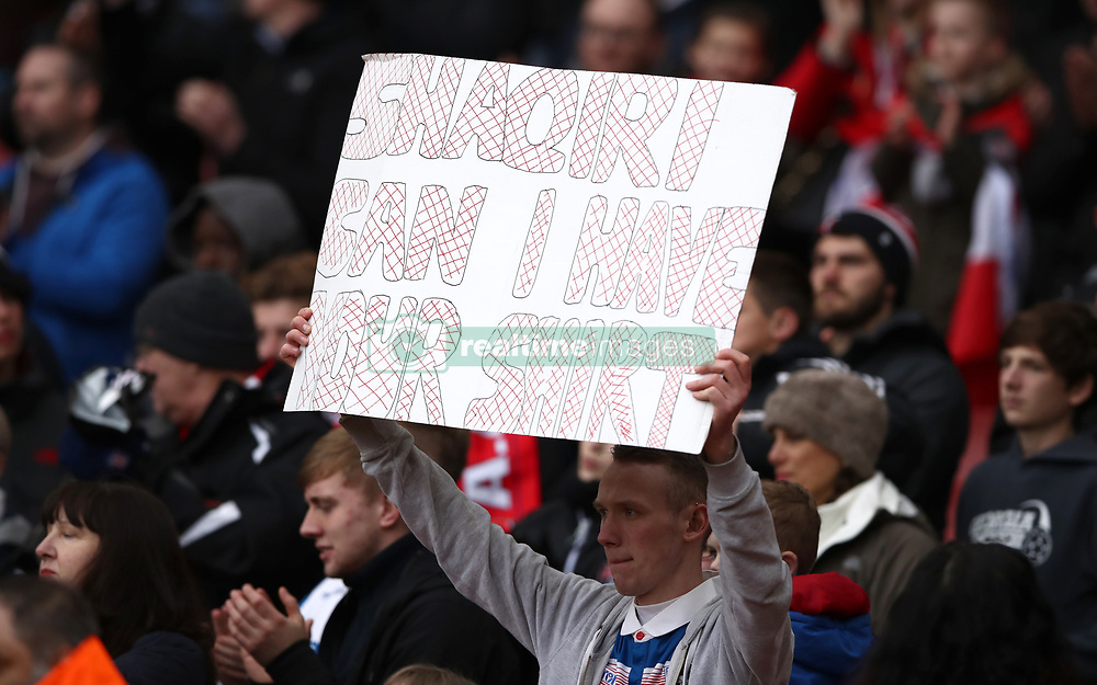 A fan holds up a sign asking for Stoke City's Xherdan Shaqiri's shirt during the Premier League match at The Emirates Stadium, London.