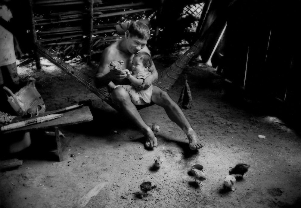 """""""Afectados"""" (Affected Ones): A Huaorani grandfather, suffering from a skin condition, spends quiet time with his grandchild in a traditional thatched structure.  He says that """"petroleros"""", or oil company workers, suggested that petroleum be used as a skin lotion.  It was presented to him as one of the """"benefits"""" that oil exploration would bring to the village of Yawapare off of Via Auca.  Then, he developed patches of irritation on his legs.  Yawepare, Ecuador.<br /> Via Auca is a road that extends south from the city of Coca.  Coca began as a solitary airstrip for a military outpost in the mid-1960's.  The Huaorani were referred to as the """"Aucas"""" or """"savages"""" by their indigenous neighbors, the Kichwa.  The Via Auca, which extends south from Coca opened up territory where the """"uncontacted"""" lived."""