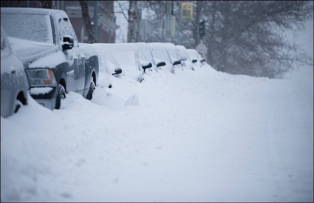 Row of cars buried along the side of the road in Midtown Kansas City, MO after a major snow storm.