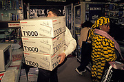 A shop assistant carries three boxes of Toshiba T1000 Portable Personal Computer laptops in an electronics and tech shop on the Tottenham Court Road, on 3rd March 1990, in London, England. The T1000 was a portable computer manufactured by the Toshiba Corporation from 1987. It had a similar specification to the IBM PC Convertible, with a 4.77 MHz 80C88 processor, 512 kB of RAM, and a monochrome CGA-compatible LCD. Unlike the Convertible, it includes a standard serial port and parallel port, connectors for an external monitor, and a real-time clock.
