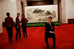 epa06270818 A Chinese security officer gestures as hostesses walk inside the Great Hall of the People (GHOP) where the 19th National Congress of the Communist Party of China (CPC) will be held in Beijing, China, 17 October 2017. The five-yearly 19th National Congress of the Communist Party of China (CPC) will begin on 18 October.  EPA-EFE/HOW HWEE YOUNG