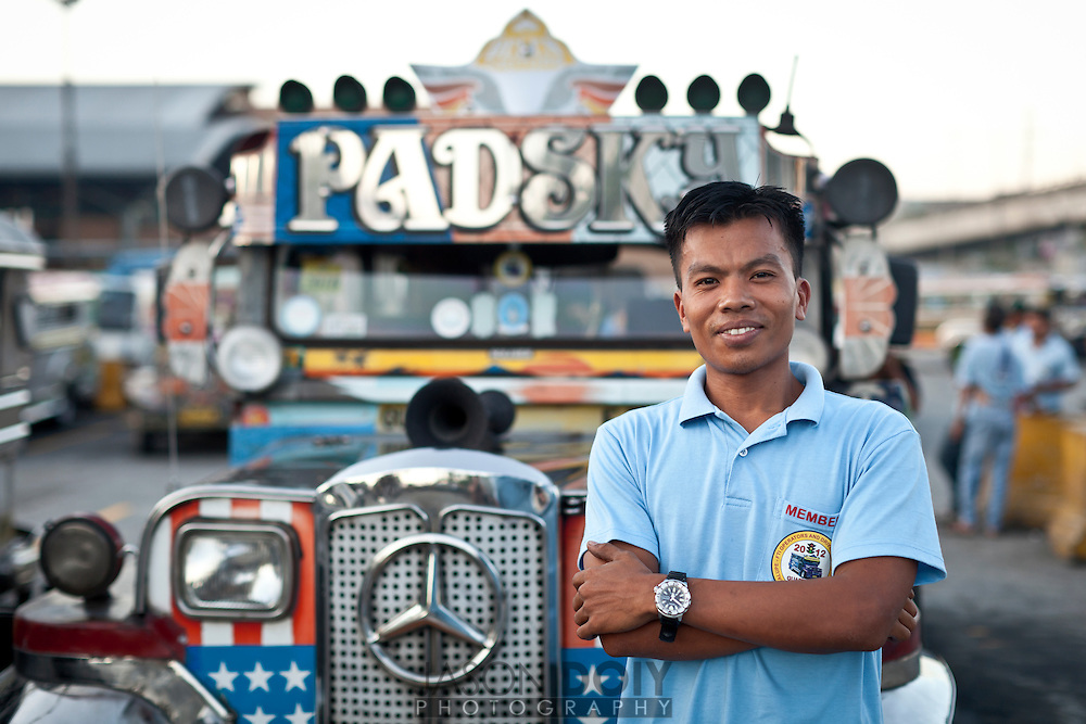 "Manila, Republic of the Philippines - April 20, 2012: A driver stands in front of his jeepney, named ""Padsky"" waiting for riders at Market Market an outdoor mall in Manila. Jeepney's are holdovers from World War II and were modified to accomadate multiple passangers and now serve as commercial transportation vehicles. They are known for their flamboyant designs and have become a symbol of Philippine culture."