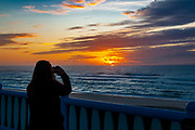 Silhouette of a woman is photographing an Atlantic Ocean Sunset. At Vieira de Leiria. A Portuguese village and also a parish in the municipality of Marinha Grande, Portugal