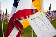 """10 SEPTEMBER 2011 - TEMPE, AZ:     A card memorializing a person killed in the attack on the World Trade Center on a flag in the """"Healing Field"""" in Tempe, AZ. The """"Healing Field,"""" a display of 2,996 flags, one for each person killed in the September 11 terrorists attacks on the World Trade Center in New York City and Washington DC, have become an annual tradition in Tempe. The event is sponsored by the National Exchange Club.      PHOTO BY JACK KURTZ"""