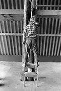 Man painting a wooden pillar, at Glastonbury, 1989.