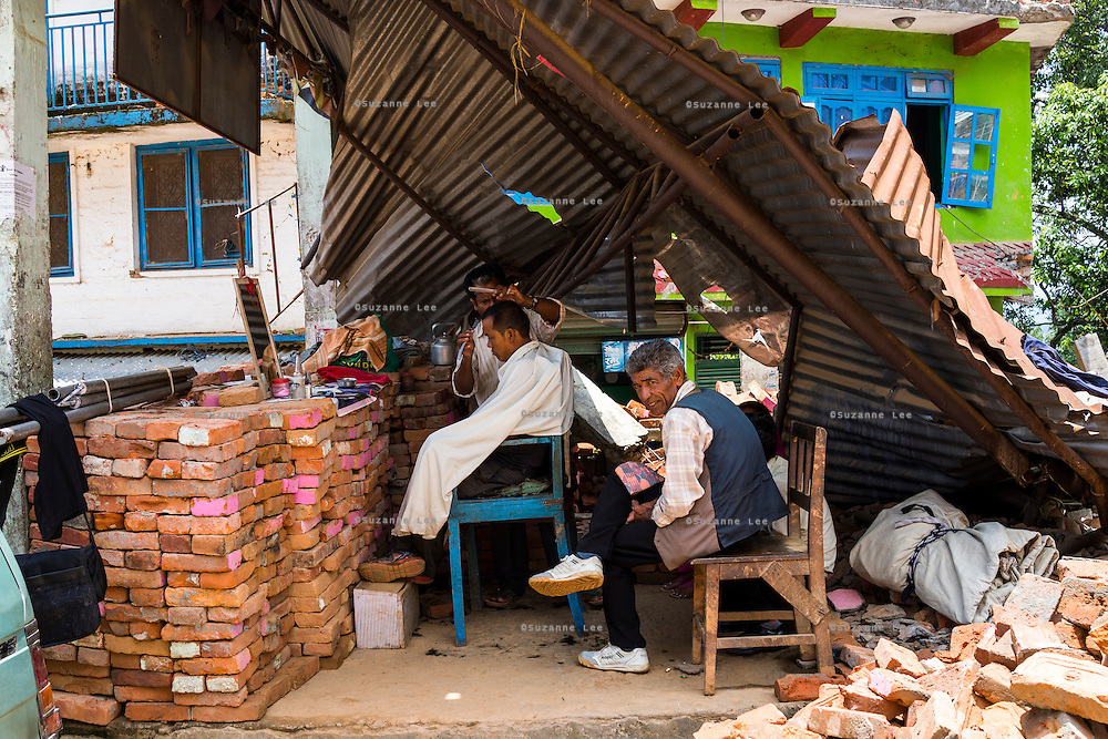A barber reopens his shop despite the destroyed structures in Chautara, Sindhupalchowk, Nepal on 29 June 2015. Sindhupalchowk was one of the most devastated by the April 25th earthquake and aftershocks that killed over 8000 people and injured over 19000 people, destroying over half a million houses. Photo by Suzanne Lee for SOS Children's Villages