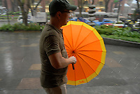 Man with an orange umbrella during a storm in Singapore.