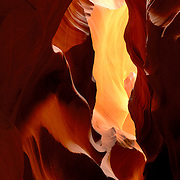 The Navajo name for Upper Antelope Canyon is Ts&eacute; bigh&aacute;n&iacute;l&iacute;n&iacute;, which means &quot;the place where water runs through rocks.&quot; <br /> <br /> Antelope Canyon was formed by erosion of Navajo Sandstone, primarily due to flash flooding and secondarily due to other sub-aerial processes. Rainwater, especially during monsoon season, runs into the extensive basin above the slot canyon sections, picking up speed and sand as it rushes into the narrow passageways. Over time the passageways eroded away, making the corridors deeper and smoothing hard edges in such a way as to form characteristic 'flowing' shapes in the rock.