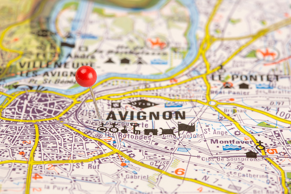 Red pin stuck into a map showing the ancient town of Avignon in France