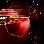 Apple sliced at high speed emitting splashes of apple juice Ray Massey is an established, award winning, UK professional  photographer, shooting creative advertising and editorial images from his stunning studio in a converted church in Camden Town, London NW1. Ray Massey specialises in drinks and liquids, still life and hands, product, gymnastics, special effects (sfx) and location photography. He is particularly known for dynamic high speed action shots of pours, bubbles, splashes and explosions in beers, champagnes, sodas, cocktails and beverages of all descriptions, as well as perfumes, paint, ink, water – even ice! Ray Massey works throughout the world with advertising agencies, designers, design groups, PR companies and directly with clients. He regularly manages the entire creative process, including post-production composition, manipulation and retouching, working with his team of retouchers to produce final images ready for publication.