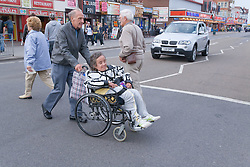 Wheel chair user and carer crossing a road whilst on a day trip