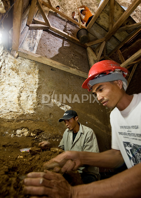"Benyamin Tarus carefully excavates archaeological remains, very close to where he unearthed the type specimen of Homo floresiensis, the Flores ""hobbit"""