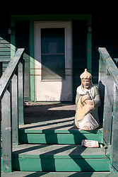 25 Oct, 2005. New Orleans, Louisiana. Hurricane Katrina aftermath.<br /> The 8th ward lies in ruins following Katrina's devastating floods. A statue guards the front door of a home with 'coffee' stain flood marks on the front door.<br /> Photo; ©Charlie Varley/varleypix.com