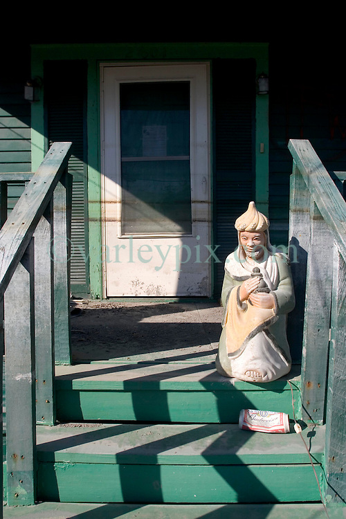25 Oct, 2005. New Orleans, Louisiana. Hurricane Katrina aftermath.<br /> The 8th ward lies in ruins following Katrina's devastating floods. A statue guards the front door of a home with 'coffee' stain flood marks on the front door.<br /> Photo; &copy;Charlie Varley/varleypix.com