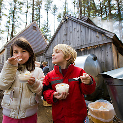 Two kids enjoy maple sundaes at Folsom's Sugar House in Chester, New Hampshire.  Steam from boiling sap rises from the sugar house.