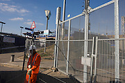 Contractor resets wire barrier to pedestrians at electrified perimeter fence at the 2012 Olympic construction site in Stratford.