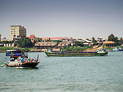 26 FEBRUARY 2015 - PHNOM PENH, CAMBODIA: A boat hauling freight passes a passenger ferry crossing the Mekong River on the outskirts of Phnom Penh.    PHOTO BY JACK KURTZ